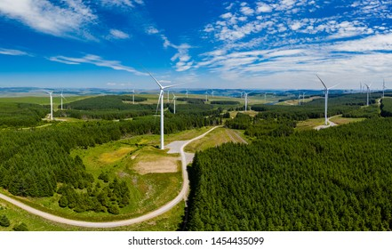 Aerial drone panorama of turbines at a large onshore windfarm in Wales, UK