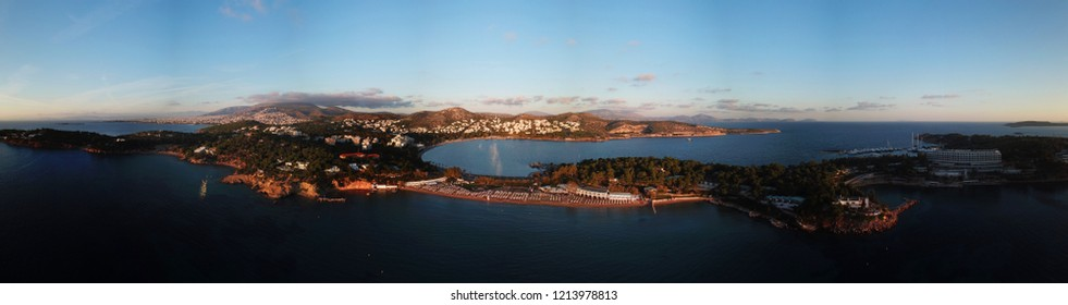 Aerial drone panoramic photo of famous luxury beach of Asteras or Astir in the heart of Vouliagmeni at sunset, Athens riviera, Attica, Greece