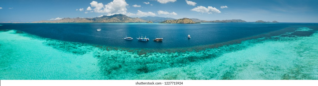 Aerial drone panoramic shot ocean, Komodo background. Transparent turquoise water of the Pacific ocean with the boats taken for tourist reasons. Komodo National Park, Indonesia.