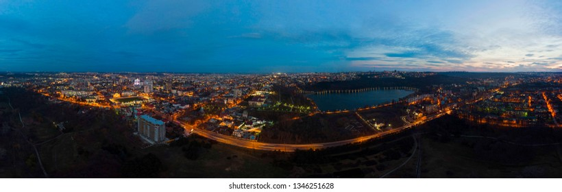 Aerial drone panoramic view of Chisinau cityscape with lights at night, blue hour at valea morilor lake, Moldova