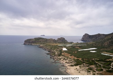 Aerial drone panoramic view of Falasarna on Crete island, Greece. Plain is used for agriculture: greenhouses and gardens of olive trees. in summer