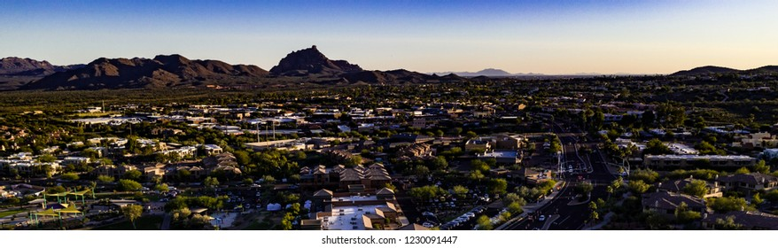 Aerial, drone, panoramic view over Fountain Hills Lake in Fountain Hills, Arizona with beautiful landscaped park area, clear, blue water and sky