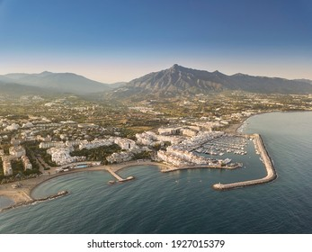 Aerial drone perspective of beautiful sunset over luxury Puerto Banus Bay in Marbella, Costa del Sol. Expensive lifestyle, luxury yachts. La concha mountain in background. Nueva Andalucía area