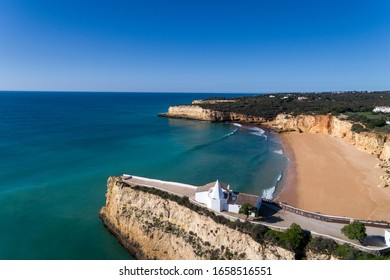 Aerial drone photo of the beaitiful Praia da Senhora da Rocha (Senhora da Rocha Beach) with the white chapel on the roks, near Armacao de Pera, Algarve, Portugal