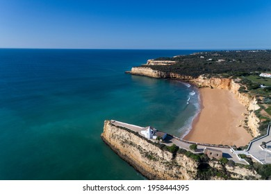 Aerial drone photo of the beaitiful Praia da Senhora da Rocha (Senhora da Rocha Beach) with the white chapel on the roks, near Armacao de Pera, Algarve, Portugal