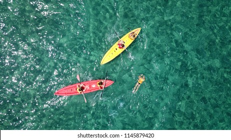 Aerial drone photo of colourful sport canoes as shot from above in turquoise clear sea