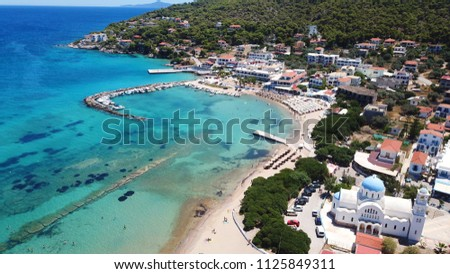 Aerial drone photo of famous port and beach of Skala and iconic church of Agioi Anargiroi, Agistri island, Saronic gulf, Greece