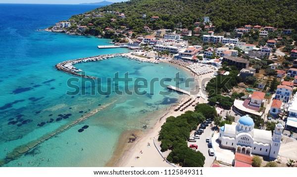 Aerial drone photo of famous port and beach of Skala and iconic church of Agioi Anargiroi, Agistri island, Saronic gulf, Greece