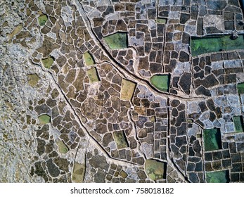 Aerial drone photo - The famous Salt Pans on the island of Gozo, Malta.  Mediterranean Sea.