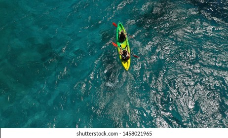 Aerial drone photo of fit couple practising on a colourful canoe in turquoise open ocean bay with crystal clear sea