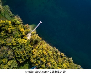 Aerial drone photo of green tree crones growing in lake shore, mixed autumn forest like a design pattern, top down view, countryside with tiny houses and piers on blue lake, privacy and tranquility
