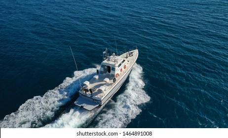 Aerial drone photo of Hellenic Coastguard powerboat cruising in high speed in deep blue Aegean sea