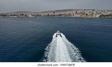 Aerial drone photo of Hellenic Coastguard powerboat cruising in high speed near port of Piraeus, Attica, Greece