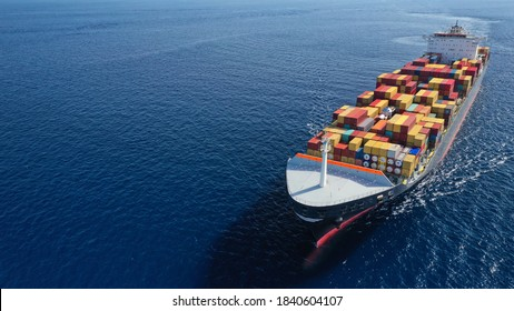 Aerial drone photo of huge container tanker ship carrying truck size colourful containers in deep blue open ocean sea - Shutterstock ID 1840604107