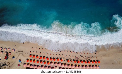 Aerial drone photo of iconic beach of Petani with rocky steep cliffs and beautiful turquoise wavy sea and sunbeds, Cefalonia island, Ionian, Greece