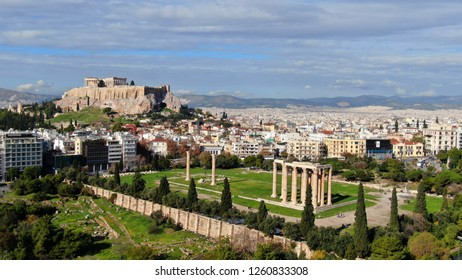 Aerial drone photo of iconic pillars of Temple of Olympian Zeus and world famous Acropolis hill with masterpiece Parthenon on top at the background, Athens historic center, Attica, Greece