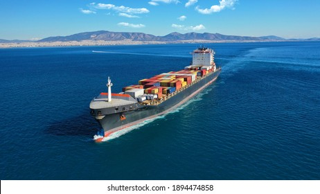 Aerial drone photo of industrial colourful vessel carrying heavy truck size containers cruising the Aegean deep blue sea - Shutterstock ID 1894474858