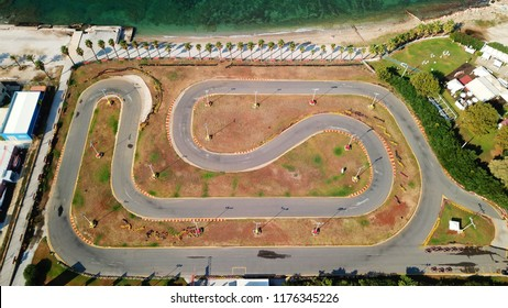 Aerial drone photo of kart track next to the ocean with sandy beach and coconut trees