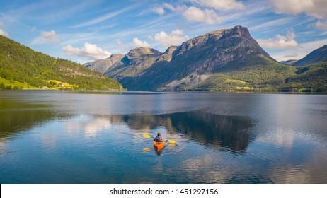 Aerial drone photo of kayaking woman. Kayaking in Norway. Amazing, senic glacier Lake in Norway. Morning Scenery.