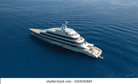 """Aerial drone photo of latest technology modern silver mega yacht and the only hybrid one called """"Savannah"""" yacht anchored near port of Mykonos, Cyclades, Greece"""