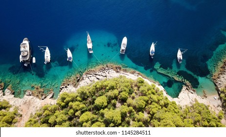 Aerial drone photo of luxury sail boats and yachts docked in paradise Ionian island turquoise clear water beach