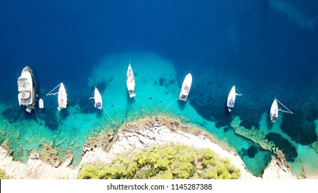 Aerial drone photo of luxury sail boats and yachts docked in turquoise clear water rocky seascape in traditional village of Assos, Cefalonia, Ionian islands, Greece