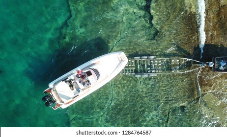 Aerial drone photo of luxury speed boat being taken out of water by trailer in tropical rocky marina
