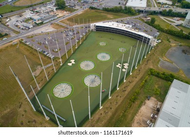 Aerial drone photo of a modern golf driving range with perimeter net