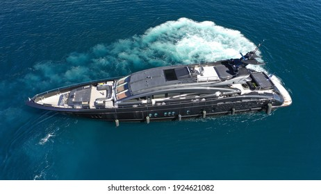 Aerial drone photo of modern yacht preparing to speed in Mediterranean port with deep blue sea