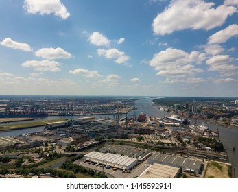 Aerial drone photo over shipyard and warehouses towards the container harbor with crane machinery and container ships in Hamburg, Germany