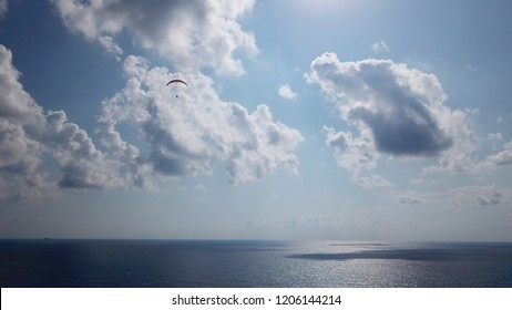 Aerial drone photo of paragliding in cloudy blue sky. Paraglider colourful tandem flying over deep turquoise mediterranean sea and mountains in bright sunny day