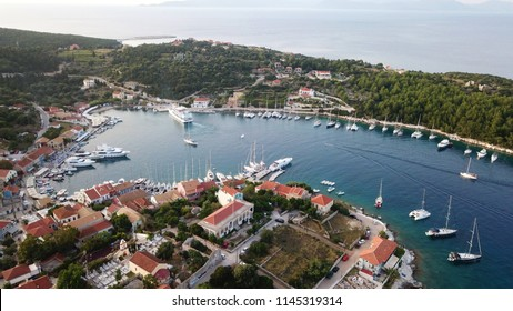 Aerial drone photo of picturesque and iconic port of Fiskardo with luxury boats docked and traditional character at sunset, Cefalonia island, Ionian, Greece
