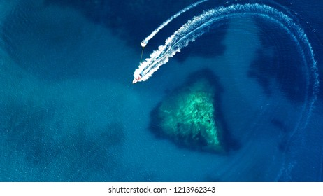 Aerial drone photo of power boat cruising in high speed in tropical emerald clear water sea