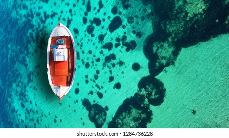 Aerial drone photo of red traditional fishing boat as seen from top in iconic beach of Super Paradise, Mykonos island, Cyclades, Greece