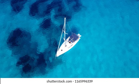 Aerial drone photo of sail boat docked in tropical mediterranean bay with crystal clear turquoise sea