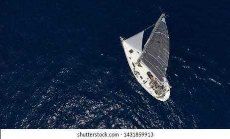Aerial drone photo of sail boat cruising the deep blue Aegean sea, Greece