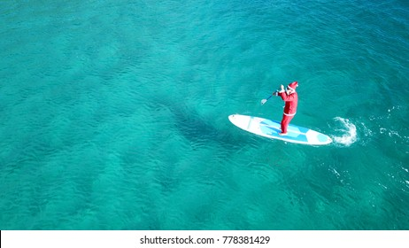 Aerial drone photo of Santa Claus in a paddle surf board known as Sup surfing in turquoise clear waters