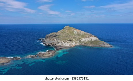 Aerial drone photo of small rocky islet of planitis near picturesque fishing village and small harbour of Panormos, Tinos island, Cyclades, Greece