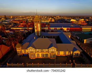 Aerial drone photo sunset view of old vintage beautiful historical Woermann Haus in coast town Swakopmund off B2 highway in summer at the western coast of Namibia, southern Africa