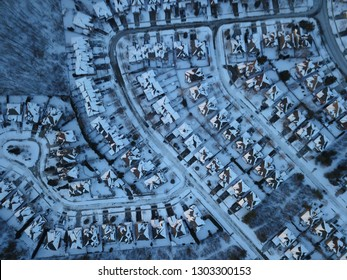 Aerial drone photo, top down, of suburban houses in Oakville, Ontario, Canada everything is white and covered with snow in the sunshine.