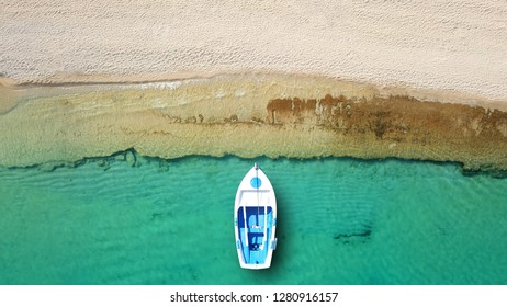 Aerial drone photo of traditional fishing boat as seen from top in iconic beach of Super Paradise, Mykonos island, Cyclades, Greece