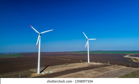 Aerial drone photo of two 2 wind turbines in plowed fields  during spring time in Edinets, Moldova