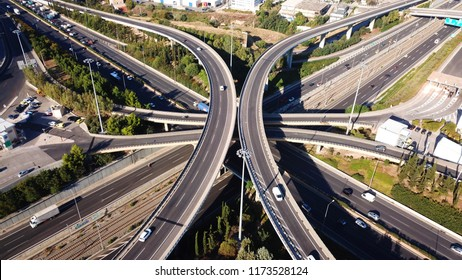 Aerial drone photo of urban elevated road junction and interchange overpass in city with light traffic