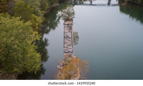 Aerial Drone Photo View Potomac River, Maryland and Unusual Green Tree Growing Abandoned Dilapidated Brick Concrete Stone Pillar Pedestal Ruin Remains of Old Historical Bridge with Reflection on Water