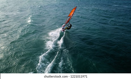 Aerial drone photo of wind surfer cruising in high speed in tropical ocean bay with deep blue see