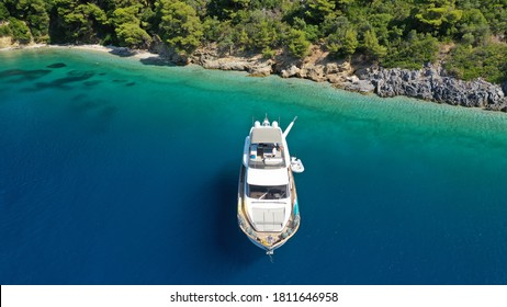 Aerial drone photo of yacht anchored in famous crystal clear bay and turquoise beach of Panormos, Skopelos island, Sporades, Greece