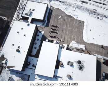 Aerial drone photograph of an elementary school with children on the blacktop.  Shot on a sunny day in winter, snow on the ground.