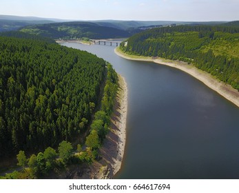 Aerial drone photography with a lake between mountains covered by forest with old tall fir tress in national park harz from germany, very good summer weather.