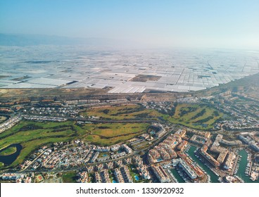 Aerial drone photography view Almerimar town with their great amount of greenhouses, growing cultivated vegetables and fruits such as tomatoes, peppers, cucumbers zucchinis. Almeria, Andalucia, Spain