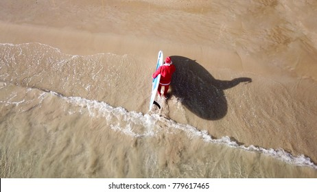 Aerial drone of Santa Claus coming out of Caribbean turquoise clear water beach holding surf board